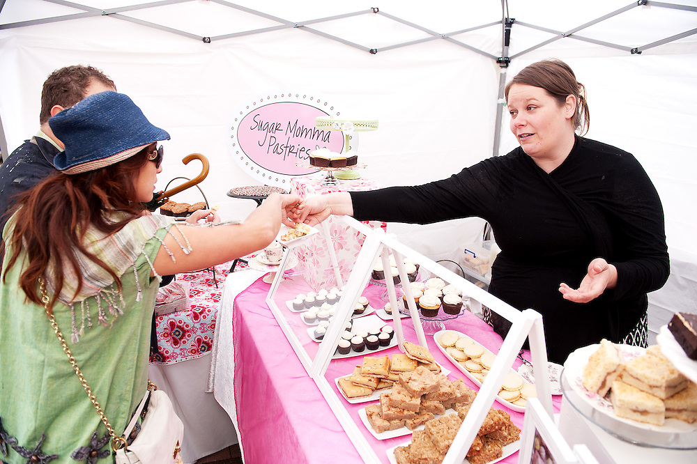 Hailey Guille hands out samples at the Sugar Mama Pastry stand.  Whistler Farmer's Market.  Sunday, June 15th, 2014.<br /> <br /> Photo Credit: David Buzzard
