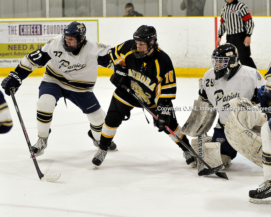 TORONTO, ON - Apr 13: Ontario Junior Hockey League, Buckland Cup Championship Series between the Aurora Tigers and the Toronto Patriots. Drake Board #10 of the Aurora Tigers battles for position with Mike Prapavessis #77 of the Toronto Lakeshore Patriots in front of Evan Buitenhuis #29 during the first period.<br /> (Photo by Shawn Muir / OJHL Images)