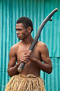 Inosi Navoto with warrior club greeting visitors to Lawai Pottery Village on Viti Levu Island, Fiji.