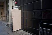 An obscured workman manhandles a wooden board sheeting into a construction site doorway, on 5th March 2019, in London, England.