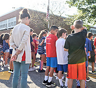 North Merrick, New York, U.S. September 11, 2019. At Park Avenue School students and staff listen to a patriotic song, and then each class with its teacher paused in front of the 9/11 Memorial Garden garden in front of the entrance, on their way back into the school. Earlier in ceremony, Principal E. Speidel of the K-6 elementary school talked about the significance of 911 and the 9/11 Memorial Garden, on the 18th Anniversary of the terrorist attacks Sept. 11, 2001.