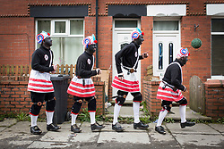 © Licensed to London News Pictures. 15/04/2017. BACUP, LANCASHIRE,  UK.  The  Morrismen of the Britannia Coconutters dance boundary to boundary in Bacup , Lancashire. In a tradition dating back hundreds of years every Easter Saturday the men have performed pagan dances to welcome Spring and ward off evil Winter spirits. The Coconutters name originates from the time when coal miners would wear coconut shells on their knees for protection in the pits. They blacken their faces  to disguise them from evil spirits  and also to reflect the coal mining traditions. <br /> <br /> Photo credit: CHRIS BULL /LNP
