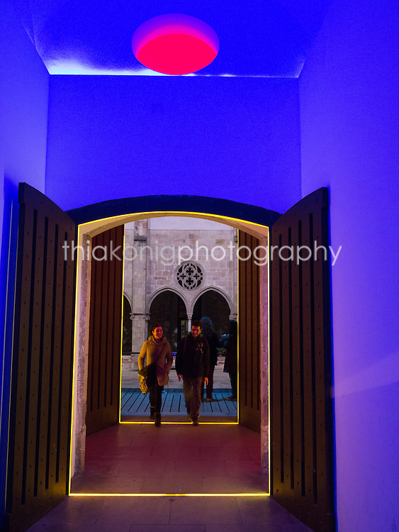 Two people walk through doorway blending gothic architecture and modern neon accents, Barcelona Spain.