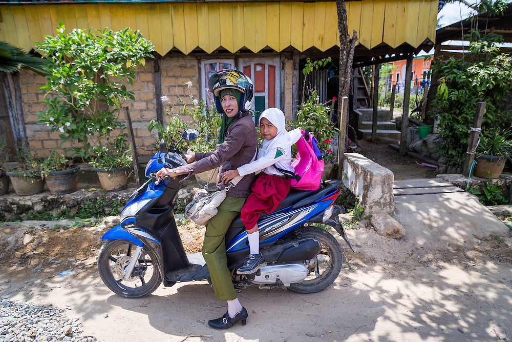 A single mother, Ibu Ratna takes her 7-year-old daughter Amel to school before going to work.