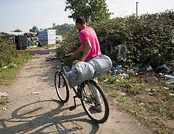© Licensed to London News Pictures. 30/08/2015. Calais, France. A vendor from Afghanistan takes supplies on his bike to go to a shop in Salam, at the other side of the refugee camp in Calais, also known as the Jungle. Tomorrow the French PM, Manuel Valls, will visit the day centre Jules Ferry at the camp. Photo credit : Isabel Infantes/LNP