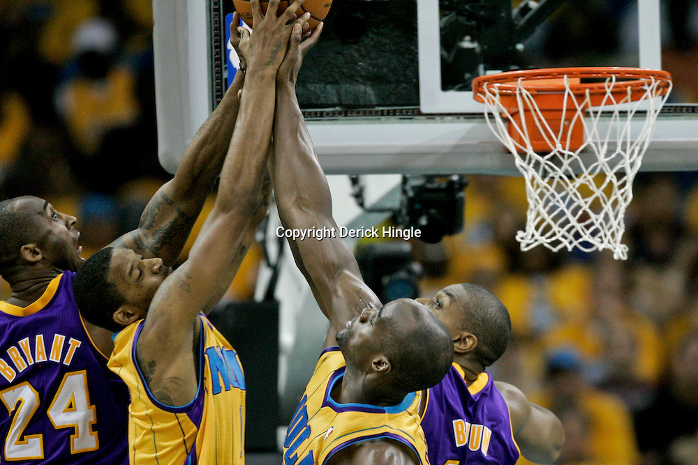 April 22, 2011; New Orleans, LA, USA; Los Angeles Lakers shooting guard Kobe Bryant (24) and center Andrew Bynum (17) along with New Orleans Hornets small forward Trevor Ariza (1) and New Orleans Hornets center Emeka Okafor (50) battle for a rebound during the second half in game three of the first round of the 2011 NBA playoffs at the New Orleans Arena. The Lakers defeated the Hornets 100-86.   Mandatory Credit: Derick E. Hingle