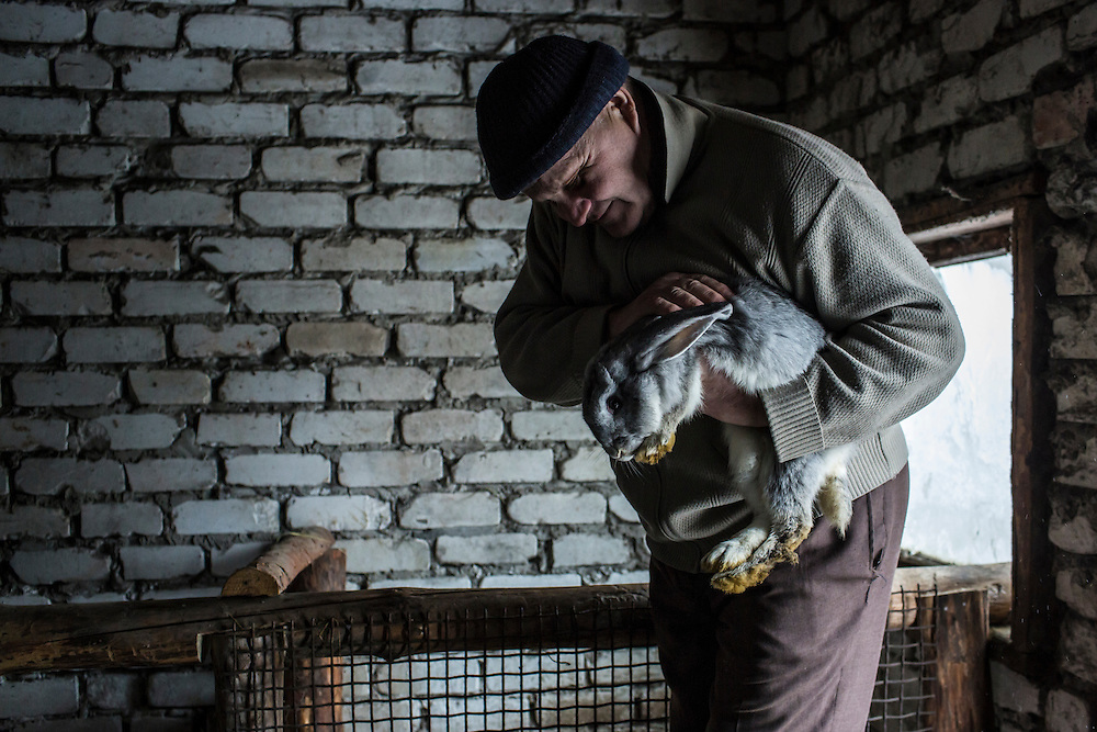 SNEZHNE, UKRAINE - JANUARY 25, 2015: Vladimir Moroz, who used to operate his own small coal mine across the street from his house, holds one of the rabbits he raises in Snezhne, Ukraine. The area is well known for its many coal mines, both large operations and small backyard operations. CREDIT: Brendan Hoffman for The New York Times