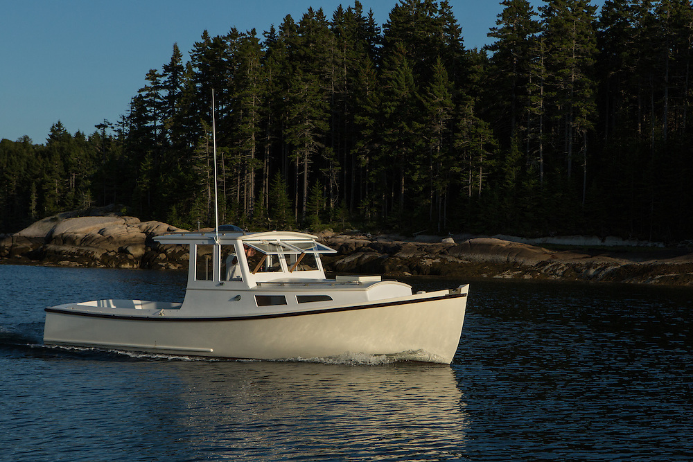 Center Harbor, Maine - 9 August 2014. A lobster boat heading out of the harbor in the late afternoon.