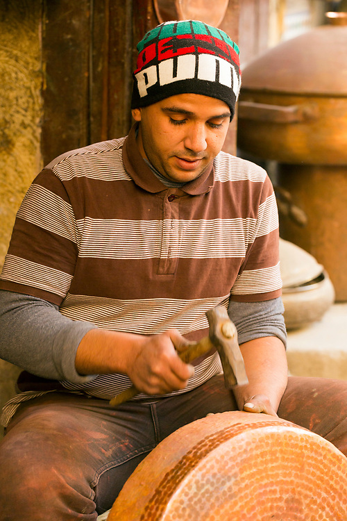 Fez, Morocco - 16th DECEMBER 2015 - Copper-smith and brass worker artisans work at a market stall selling metal pots and pans in Place Seffarine, old Fez Medina, Middle Atlas, Morocco.