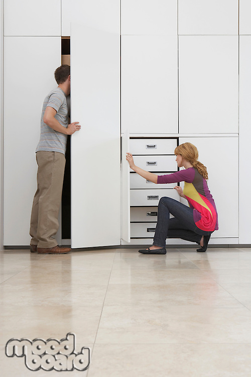 Couple looking in wardrobe in empty apartment