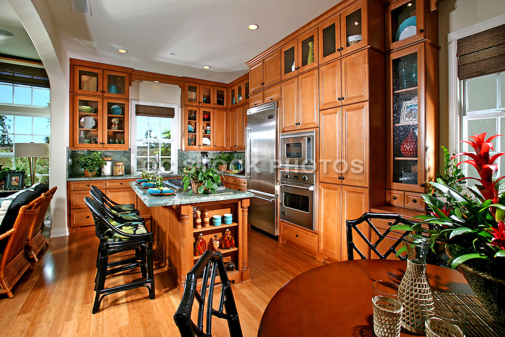 Model Home Kitchen With Hard Wood Floors and cherry Honey Cabinets
