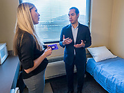 01 NOVEMBER 2019 - DES MOINES, IOWA: EMILY OSWEILER shows JULIAN CASTRO, former Secretary of Housing and Urban Development in the Obama Administration, one of the apartments at the YMCA Supportive Housing Campus in downtown Des Moines Friday. Secretary Castro, who is running for the Democratic nomination for the US presidency, toured the YMCA Supportive Housing Campus in downtown Des Moines Friday. The campus is the only project of its type in the US. It provides transitional housing in the form of individual apartments (rather than dorms) for at risk people rent is needs tested so poverty does not prevent people from getting apartments. There are about 140 apartments in the complex, the YMCA has a waiting list of 119 people. Castro toured the campus before he spoke at the Liberty and Justice Celebration downtown.            PHOTO BY JACK KURTZ