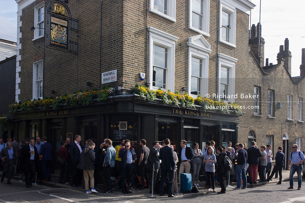 Friday evening drinkers enjoy good weather outside The Kings Arms on Roupell Street, Waterloo, south London.