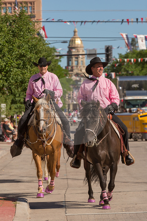 Cowboys riding in the Cheyenne Frontier Days parade past the state capital building July 23, 2015 in Cheyenne, Wyoming. Frontier Days celebrates the cowboy traditions of the west with a rodeo, parade and fair.