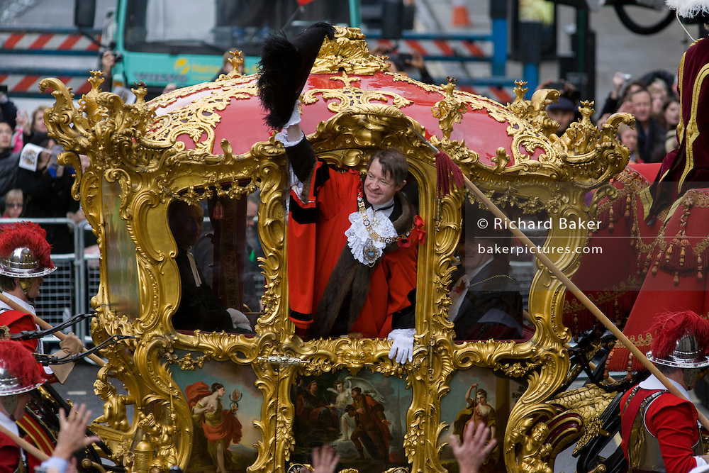 Alderman and Rt Hon The Lord Mayor of London, Roger Gifford, a merchant banker with Swedish bank SEB waves to crowds during the Lord Mayor's Show. He is the 685th in the City of London's ancient history. The new Mayor's procession consists of a 3-mile, 150-float parade of commercial and military organisations going back to medieval times. This is the oldest and longest civic procession in the world that has survived the Plague and the Blitz, today one of the best-loved pageants. Henry Fitz-Ailwyn was the first Lord Mayor (1189-1212) and ever since, eminent city fathers (and one woman) have taken the role of the sovereign's representative in the City - London's ancient, self-governing financial district. The role ensured the King had an ally within the prosperous enclave.