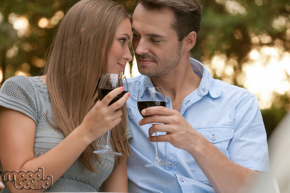 Loving young couple toasting red wine in park