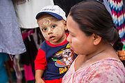 24 OCTOBER 2012 - PATTANI, PATTANI, THAILAND:  Immigrant woman from Myanmar (Burma) and her child in a street market in Pattani, Thailand. More than 5,000 people have been killed and over 9,000 hurt in more than 11,000 incidents, or about 3.5 a day, in Thailand's three southernmost provinces and four districts of Songkhla since the insurgent violence erupted in January 2004, according to Deep South Watch, an independent research organization that monitors violence in Thailand's deep south region that borders Malaysia. So far immigrants in the area, most of whom work in construction and fishing industries, have not been dragged into the violence. Muslim extremists are battling the Thai government and its symbols, like schools and Buddhist facilities.    PHOTO BY JACK KURTZ