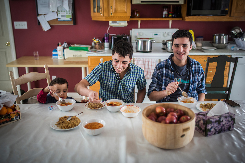 Syrian refugees and brothers, left to right Fadl Al Jasem, Ahmad, and Ramaz  eat lunch inside their temporary home in Picton, Ontario, Canada, Wednesday January 20, 2016.   (Mark Blinch for the BBC)