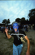 Raveller with blue painted face, silver hair and pierced tongue, Paris Techno Parade, 1999