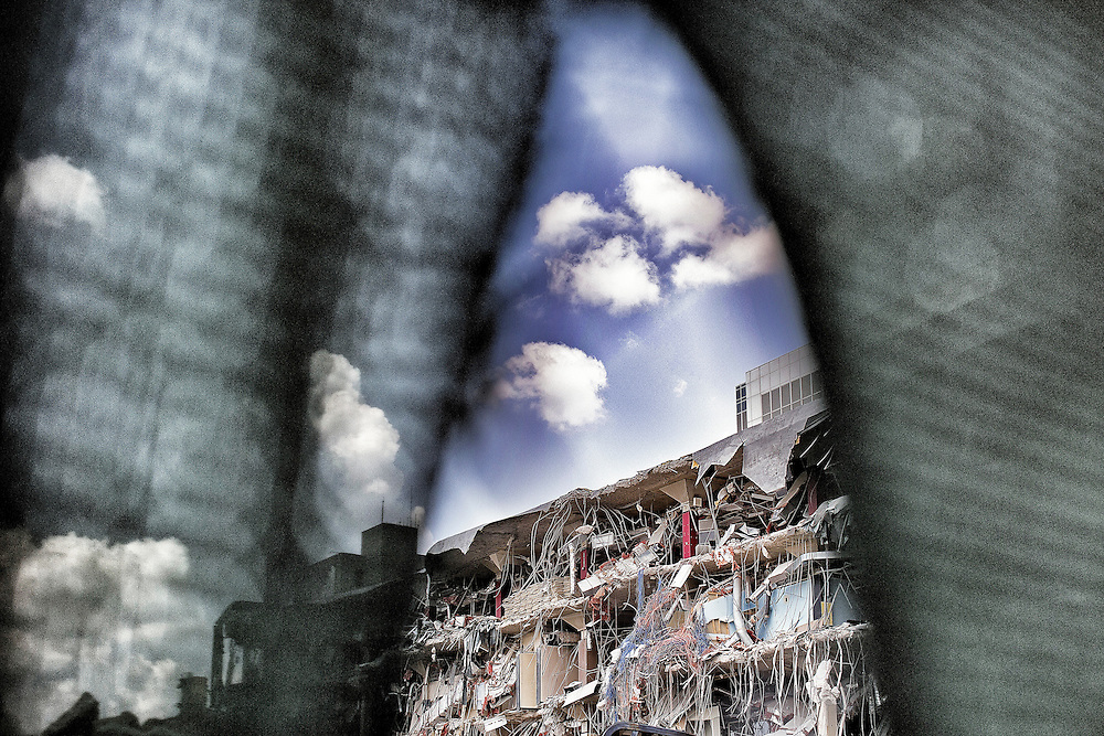 Demolition of the Charlotte Observer building photographed thru fabric covering a fence.