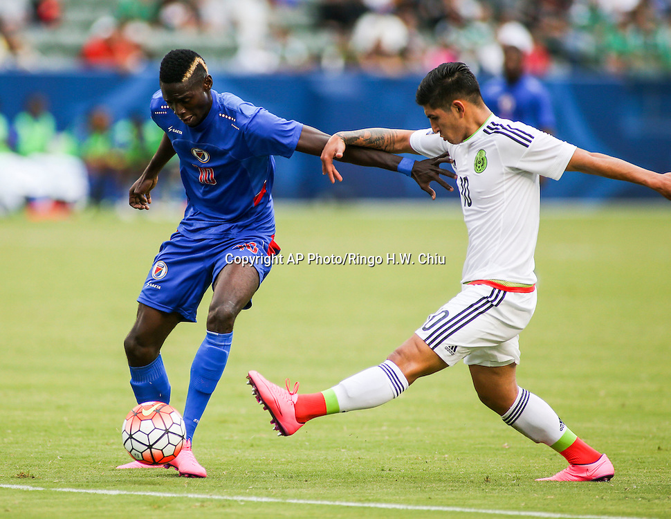 Haiti midfielder Woodensky Marlet Cherenfant #10, left, and Mexico defender Víctor Alfonso Guzmán Guzmán #10 fight for the ball in the first half of a CONCACAF men's Olympic qualifying soccer match in Carson, Calif., Sunday, Oct. 4, 2015. (AP Photo/Ringo H.W. Chiu)