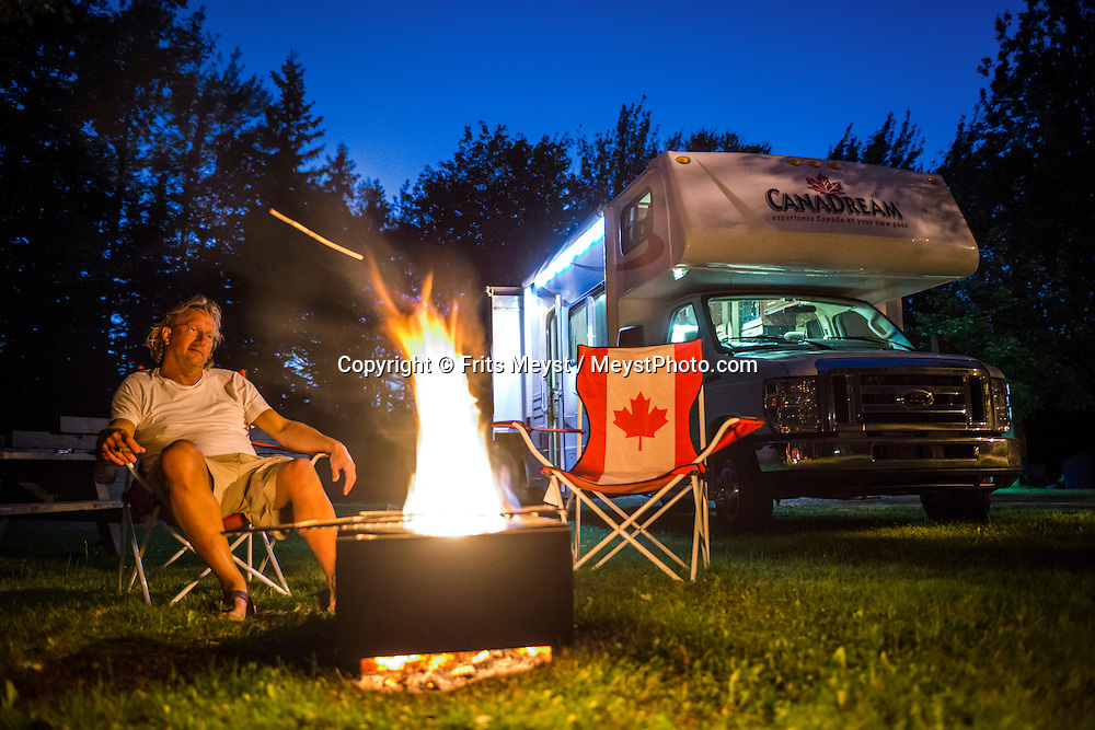 """Nova Scotia, Canada, August 2014. a campfire and RV camping at an RV campsite. Nova Scotia was one of the original four provinces that became part of Canada in 1867.  """"Nova Scotia"""" is Latin for """"New Scotland"""", and Scottish settlers brought culture and traditions that continue to this day. Photo by Frits Meyst / MeystPhoto.com"""