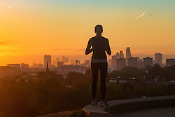 Primrose Hill, London, October 4th 2016. A woman admires the view from Primrose Hill as dawn breaks across London, throwing the city's skyline into silhouette.