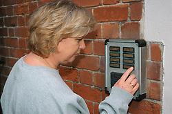 Woman using door intercom,