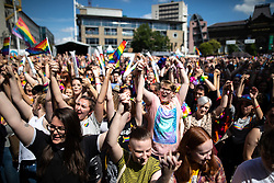 © Licensed to London News Pictures . 05/08/2018. Leeds, UK. Crowds hold hands in solidarity and protest against the lack of safe spaces in which gay couples can publicly share their affection , in Millenium Square . Leeds Gay Pride parade through the Yorkshire city's centre . Leeds's annual Gay Pride festiva celebrates the city's LGBTQ+ life and culture . Photo credit: Joel Goodman/LNP