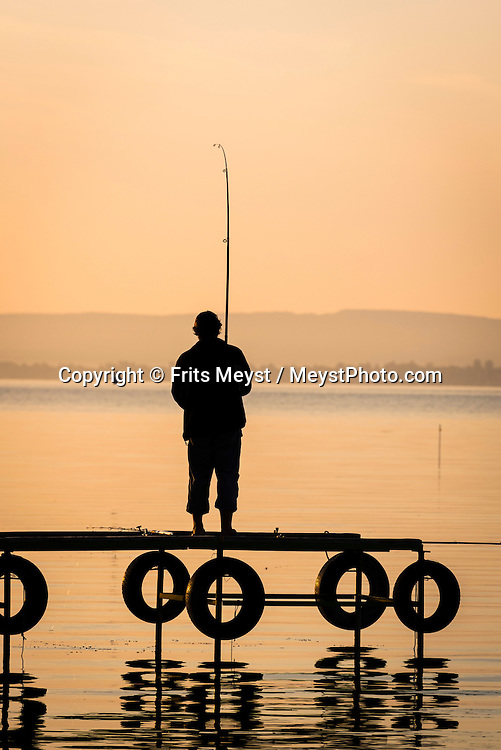 Revfulop, Balaton, Hungary, August 2015.  A fisherman at sunrise. Balatontourist Camping Napfény in Révfülöp is situated directly by lake and at few kilometres from the scenic Kali Basin, considered as the most beautiful landscape of  the Northern shore. Lake Balaton is a freshwater lake in the Transdanubian region of Hungary. It is the largest lake in Central Europe and one of the region's foremost tourist destinations. The mountainous region of the northern shore is known both for its historic character and as a major wine region, while the flat southern shore is known for its resort towns. Photo by Frits Meyst / MeystPhoto.com