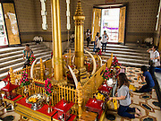 12 MARCH 2015 - BANGKOK, THAILAND:  People pray in the City Pillar Shrine in Bangkok. Bangkok's city pillar shrine (also known as San Lak Muang) is one of the most important city pillar shrines in Thailand. The shrine is in the heart of Bangkok, opposite the grand palace in the southeast corner of the Sanam Luang and close to the Ministry of Defence. The shrine was built after the establishment of the Rattanakosin Kingdom (Bangkok) to replace the old capital of the Thonburi Kingdom during the reign of King Rama I in 1782. It was intended to be the spiritual center for Thai citizens.     PHOTO BY JACK KURTZ