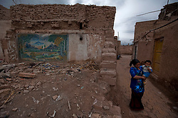 A picture made available on 27 May 2013 of a woman of the Uighur ethnic group and her child walking along a partly demolished section of the old town of Kashgar on the western edge of China's Xinjiang Uighur Autonomous Region, China 26 May 2013. Kashgar old town's historic labyrinth of earthen mud houses are rapidly being demolished and revamped in a massive government plan to transform the city since 2009. The Chinese government, citing unsafe structures and non-compliance with fire and earthquake safety regulations, has razed and rebuilt more than two thirds of the old city by 2012, relocating thousands of its mainly Uighur ethnic minority residents. Uighurs make up about the majority of the 3.9 million people living in the restive region of Kashgar where the north and south silk road met. Tensions between the Uighurs and Han Chinese have been high as they complain of cultural and religious repression and claim that ethnic Chinese migrants enjoy the main benefits of development in the oil-rich but economically backward region.