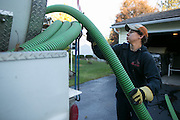 Cole Johnson of Barefoot Septic returns hoses to the pumping truck after an appointment in Caledonia, New York on Monday, October 12, 2015. Barefoot Septic & Sewer is a family-owned business, and was established in 1961.