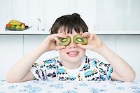 Boy (5-6) putting kiwi slices to eyes