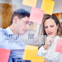 A photograph of two colleagues at a legal recruitment company making notes on post it notes on a glass wall