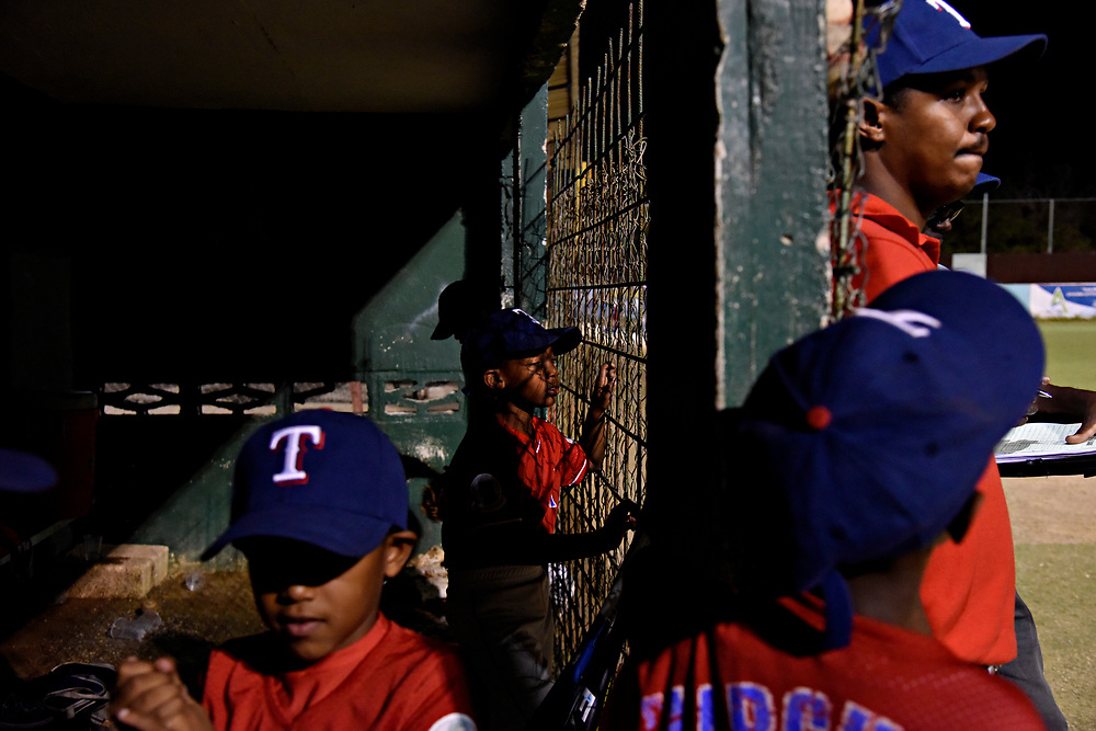 WILLEMSTAD, CURACAO - DECEMBER 10, 2014: Players and coaches watch from the dugout as the Marchena Hardware 7-9 year olds play team Trai Seru during a tournament at the Frank Curiel field. The team wears Texas Rangers hats because Rangers player Jurickson Profar's little brother Jurdrick Profar is on the team. (photo by Melissa Lyttle)