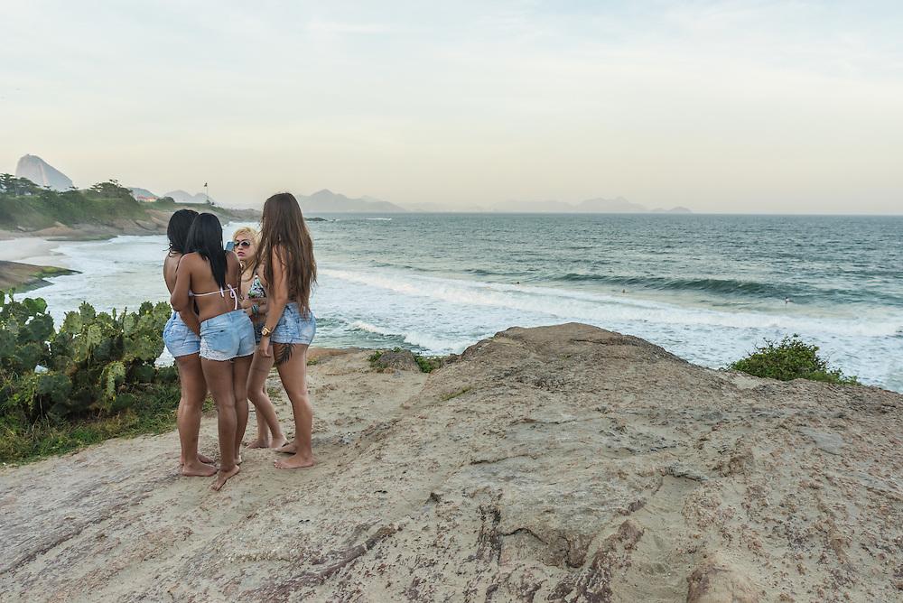Girls in skirts standing at arpoador at sunset, Ipanema beach, Rio de Janeiro, Brazil.