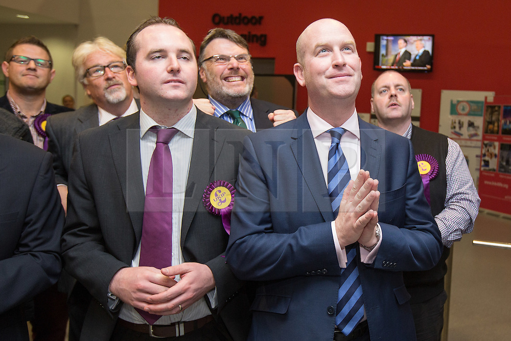© Licensed to London News Pictures . 10/10/2014 . Heywood , UK . UKIP MEP Paul Nuttall (right) holds his hands together in prayer as he watches the declaration at the Clacton count on TV . The count at the Heywood and Middleton by-election , following the death of sitting MP Jim Dobbin . Photo credit : Joel Goodman/LNP