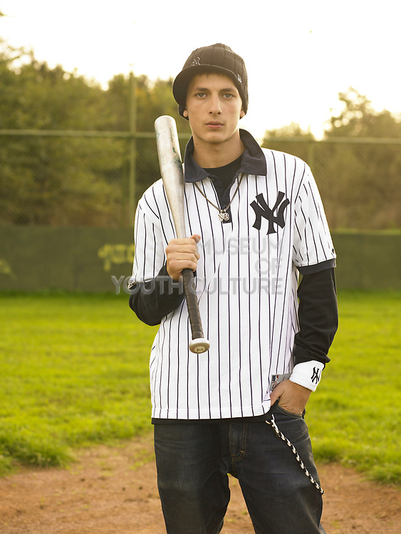Young man holding baseball bat standing on field.