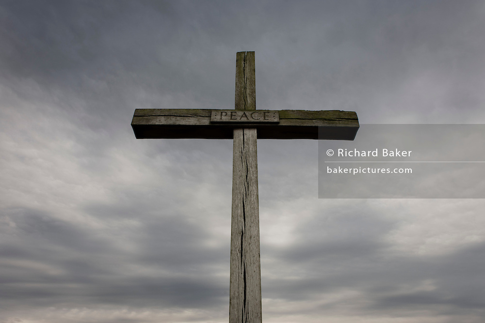 A cross made from English oak rises up into threatening grey English skies. With splits in its vertical and horizontal beams, the word Peace is written in lettering in the centre in an image of Christian values - a message for mankind, of humanity and goodwill to all Men. The wood is from the royal estate of Sandringham in Norfolk, presented in August 1987 by Queen Elizabeth II to mark the site of the high altar of the former St Benet's Abbey near Ludham on the Norfolk Broads.