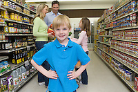 Boy stands with hands on hips with family shopping in supermarket