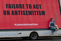 © Licensed to London News Pictures. 17/04/2018. London, UK. A woman holds her fist in the air next to one of three mobile billboards protesting against antisemitism in the Labour Party. Photo credit: Rob Pinney/LNP