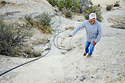 22 OCTOBER 2007 -- COYOTE CANYON, NM: MARK TSOSIE, 78 years old, a member of the Navajo Nation, checks on the piping used in his home made irrigation system in Peach Springs Wash near Coyote Canyon. Tsosie has to haul water from his well to his home and livestock. He has been hauling water all his life. He started working for the railroad when he was 14 years old. His job was to haul water to the workers. Now retired and he's still hauling water except now he hauls it to his home. More than 30 percent of the homes on the Navajo Nation, about the size of West Virginia and the largest Indian reservation in the US, don't have indoor plumbing or a regular supply of domestic water. Many of these homes have to either buy water from commercial vendors or haul water from public wells. A Federal study showed that the total cost of hauling water was about $113 per 1,000 gallons. A Phoenix household, in comparison, pays just $5 a month for up to 7,400 gallons of water. The lack of water on the reservation means the Navajo are among the most miserly users of water in the United States. Families that have to buy or haul water use only about 15 gallons of water per day per person. In Phoenix, by comparison, the average water use is about 170 gallons per day.  Photo by Jack Kurtz