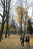 Two young women walk through Park Bedbarskiego on a late fall day in Krakow, Poland