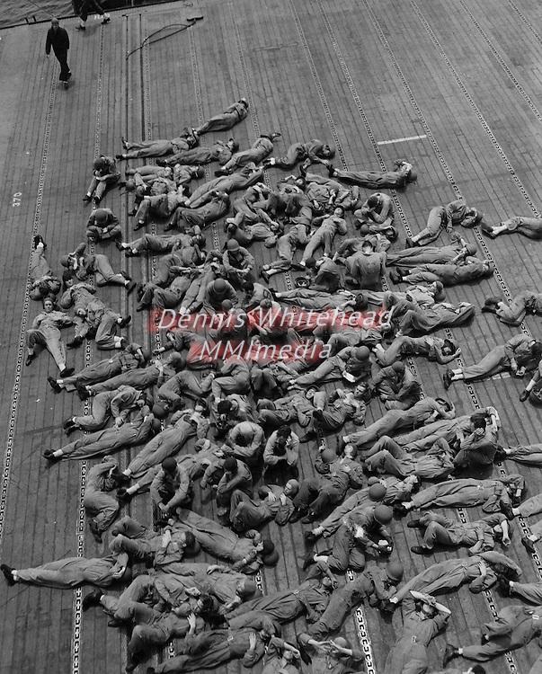 Crewmen aboard the USS Enterprise take a break on the flight deck enroute to Guadalcanal Island.