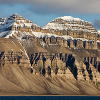 Norway, Svalbard, Spitsbergen Island, Setting midnight sun lights eroded cliffs and mountain peaks in Billefjorden along Isfjorden