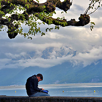 Man Sitting with Lake Geneva and Alps in Ouchy, Switzerland <br />