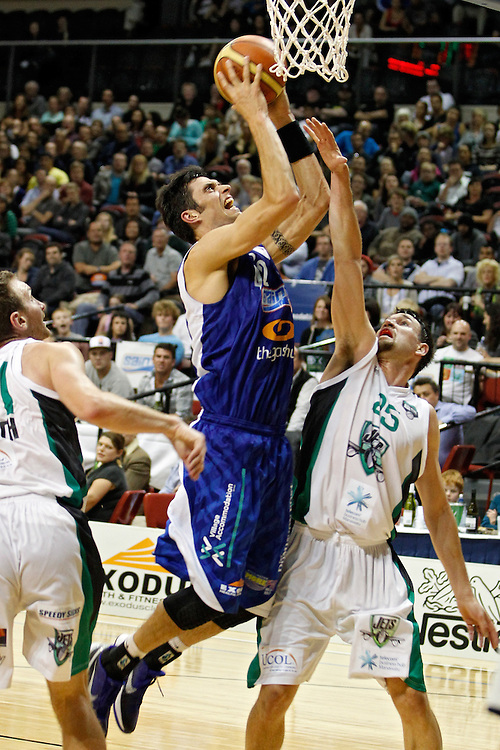 Wellington Saints' forward Arthur Trousdell, centre puts up a shot against the Manawatu Jets in the National Basketball League game, TSB Bank Arena, Wellington, New Zealand, Friday, April 27, 2012. Credit: SNPA/Dean Pemberton.