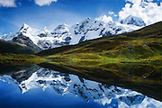 "The Cordillera Huayhuash reflects in a small lake at 15,000 feet in the Andes Mountains, Peru, South America. The highest peak on the right is Siula Grande (east face 20,800 feet or 6344 meters elevation), which was the subject of the gripping 2003 British docudrama ""Touching the Void."" In 1985, climbers Joe Simpson and Simon Yates scaled the treacherous Siula Grande, one of the last unconquered mountains in the Andes, but after Joe broke his leg, their descent became one of the most amazing survival stories in mountaineering history. This photo shows the northeast face, but they climbed Siula Grande from a valley on the other side (the west face) and descended along the north ridge, on the upper right. The 2003 movie is based upon Joe Simpson's harrowing book, ""Touching the Void: The True Story of One Man's Miraculous Survival."" At center is the peak of Carnicero (19,550 feet / 5960 meters). Tom Dempsey had this photo published in Wilderness Travel 2006 Catalog of Adventures and in 2009 on Swedish trekking company site www.adventurelovers.se."
