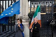 On the day that Prime Minister Boris Johnson negotiates with Brussels over a Brexit deal, and when the DUP (Democratic Unionist Party) reject his proposals, pro-European Union Brexit protesters holding the EU and Irish Republic flags position themselves beneath the British Parliament's railings at Carriage Gate on Parliament Square, on 16th October 2019, in Westminster, London, England.